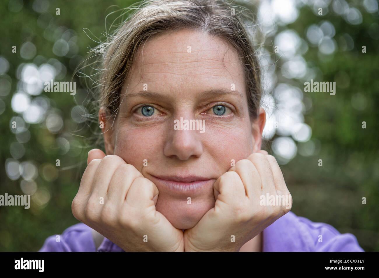 Frau, interessiert frühen 40er Jahren, unterstützt den Kopf mit den Händen, auf der Suche Stockbild