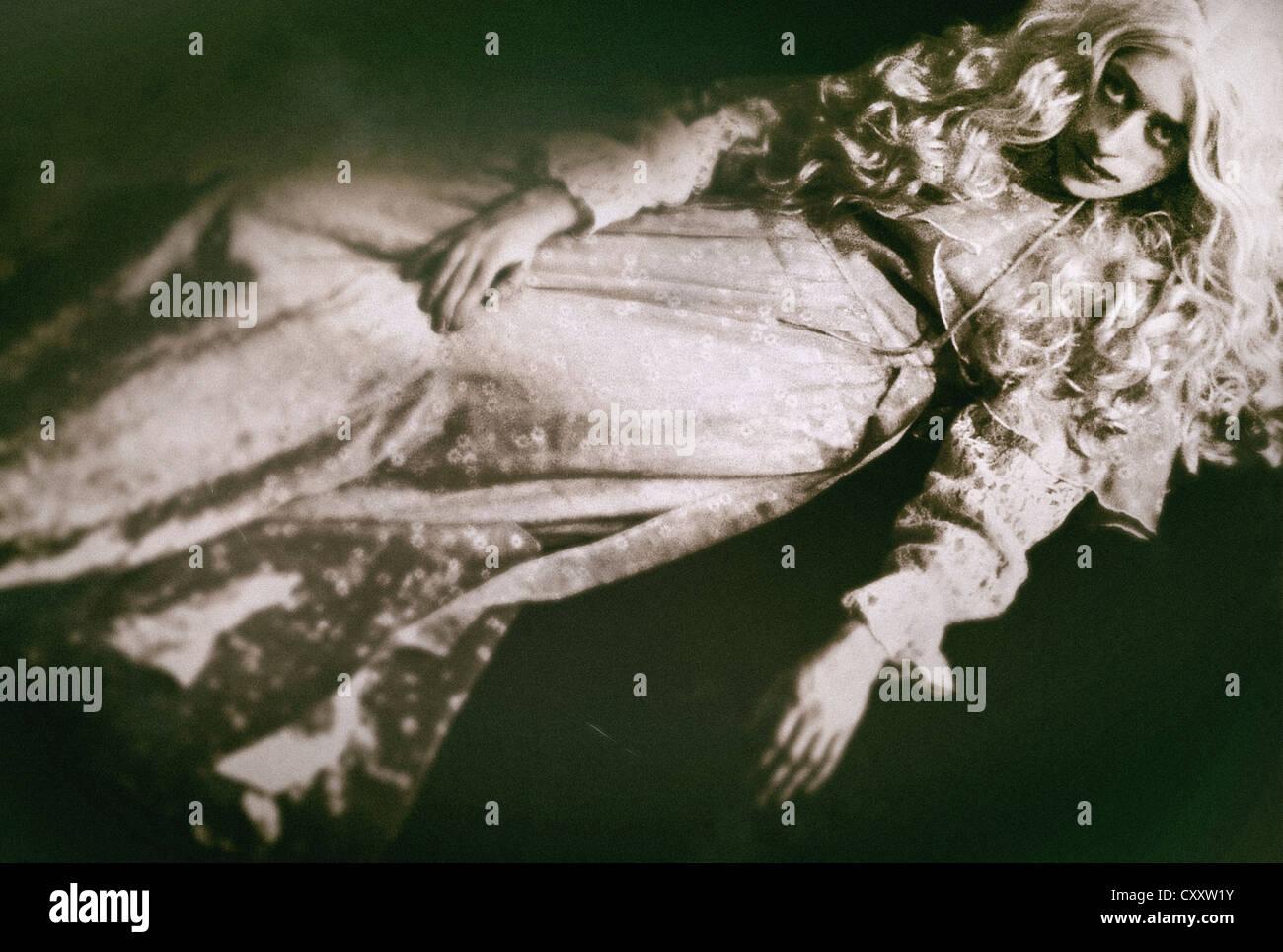 Eine Frau in einem weißen Kleid mit einem blassen Teint und weiße Haare auf dem Boden liegend, starrte Stockbild