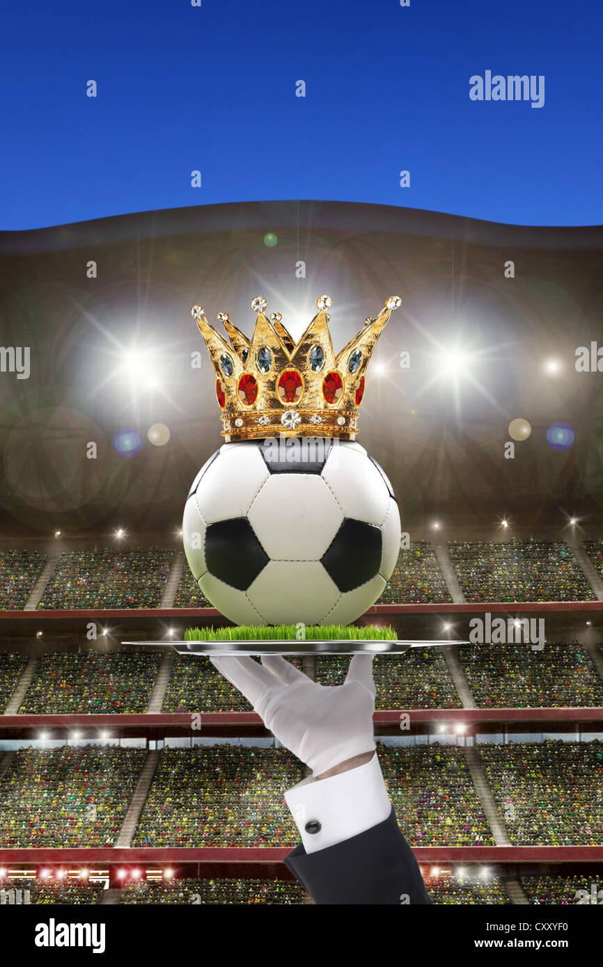 Fußball mit einer Krone statt auf einem Tablett in einem Fußballstadion mit Zuschauer steht, Abbildung Stockbild