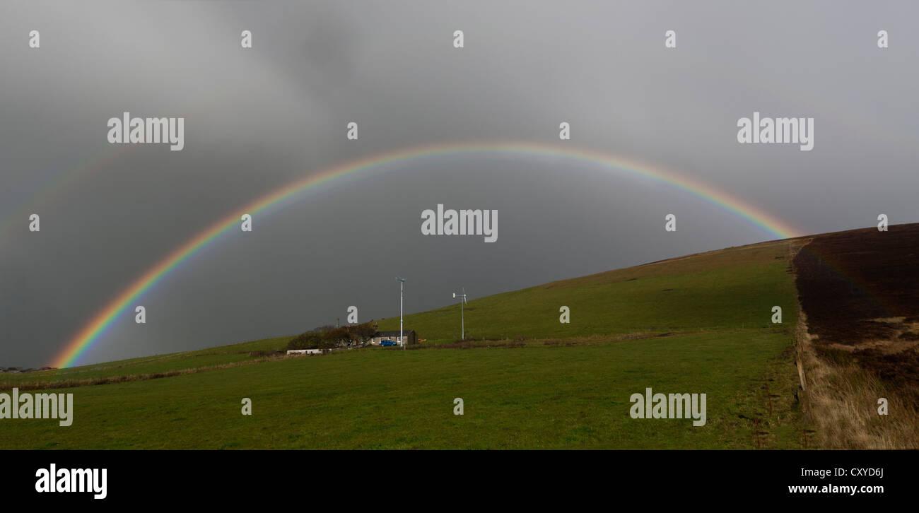 Regenbogen über Cottage mit 2 Windkraftanlagen Stockbild