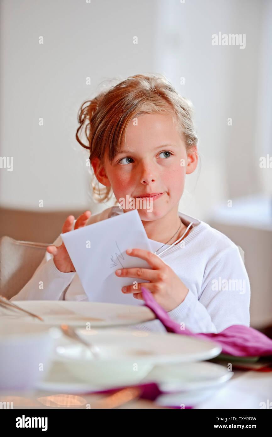 Mädchen, 9 Jahre, mit Grußkarte am Tag ihrer Erstkommunion, Region Münsterland, Nordrhein-Westfalen Stockbild