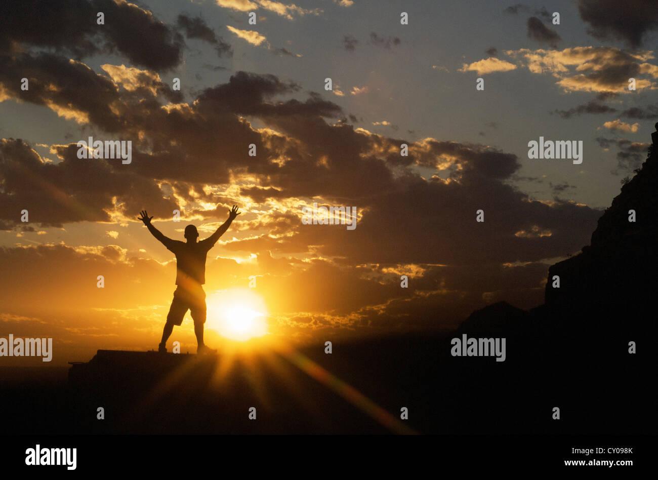 Männliche Figur mit Armen ausgestreckt stehend mit Sonnenuntergang im Hintergrund Stockbild