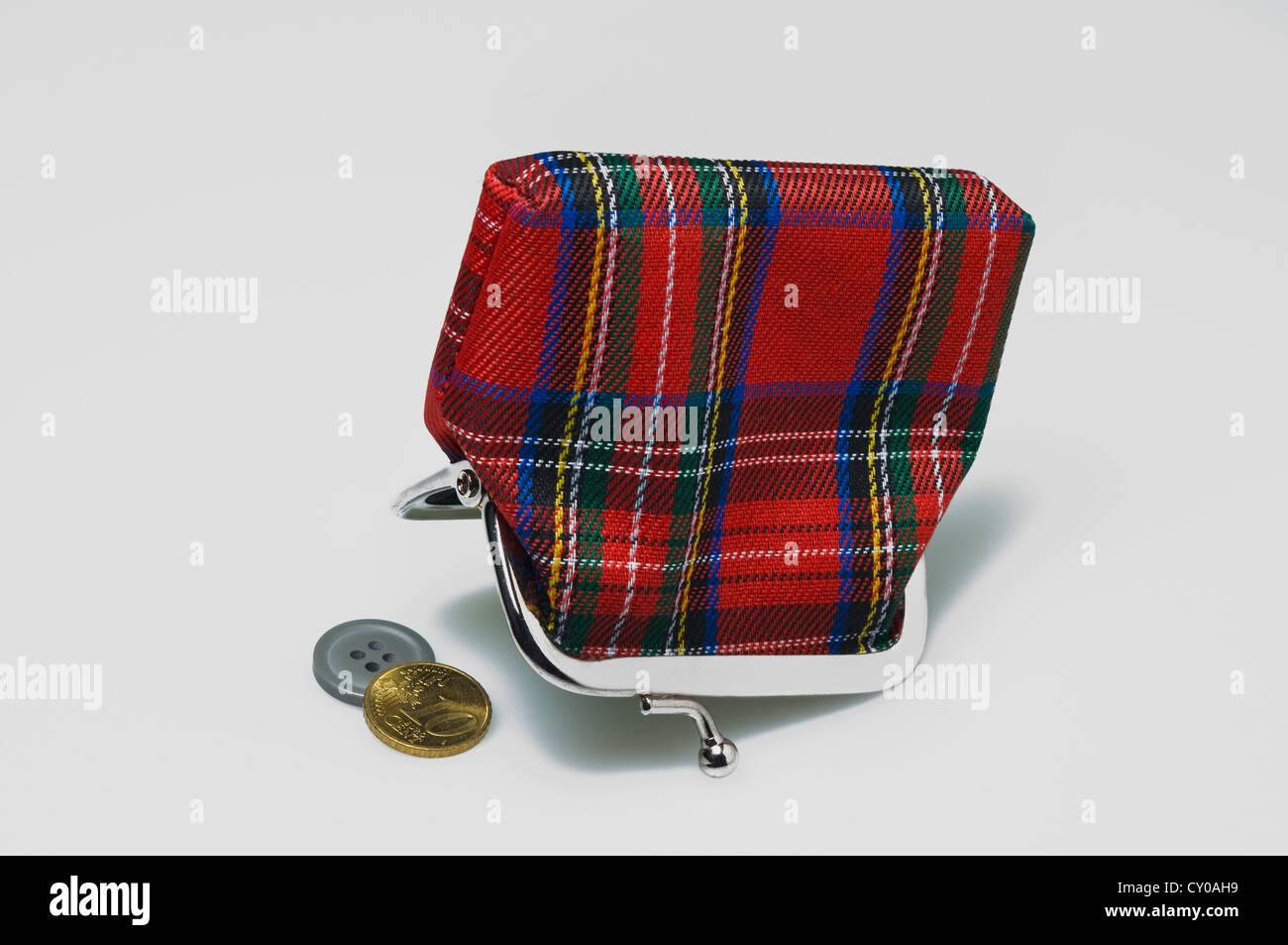 Auf den Kopf nach unten Scotsmans Geldbörse mit einer 10-Cent-Münze und eine Schaltfläche, symbolisches Stockbild