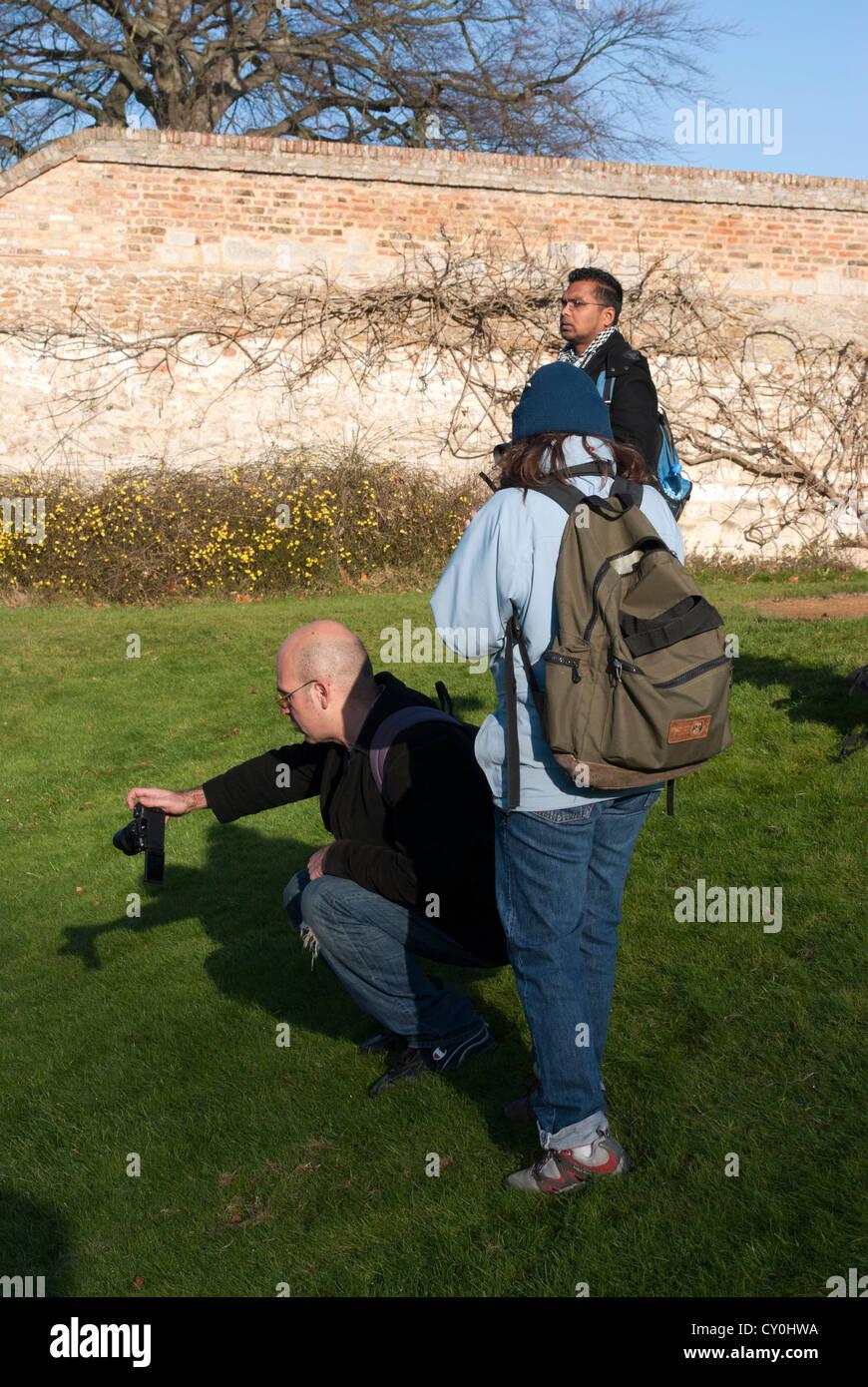 Mann nach unten um zu fotografieren mit anderen Menschen stand neben ihm hocken Stockfoto