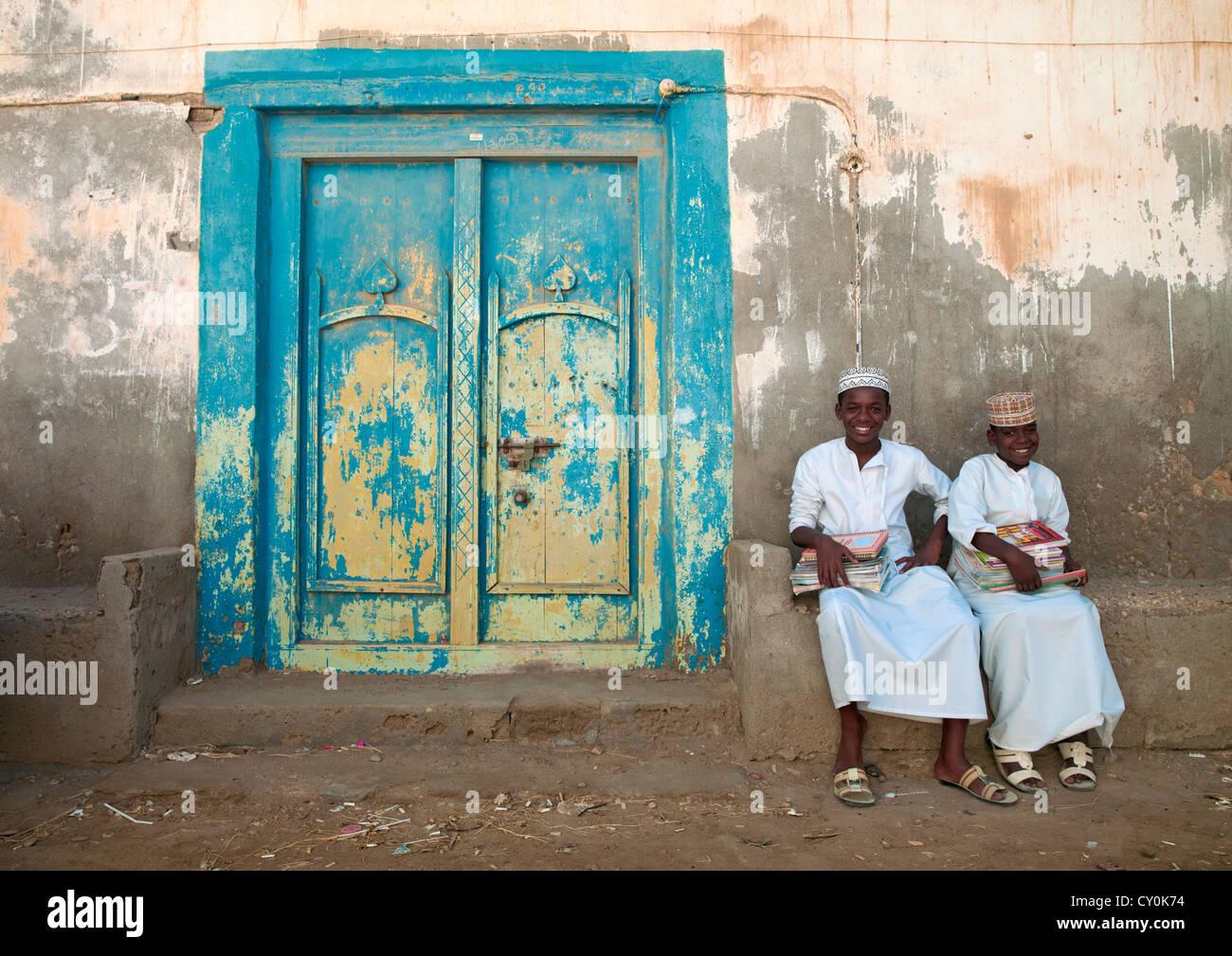 Zwei Kinder In weißen Dischdascha sitzt neben A Blau Holztür, Mirbat ...
