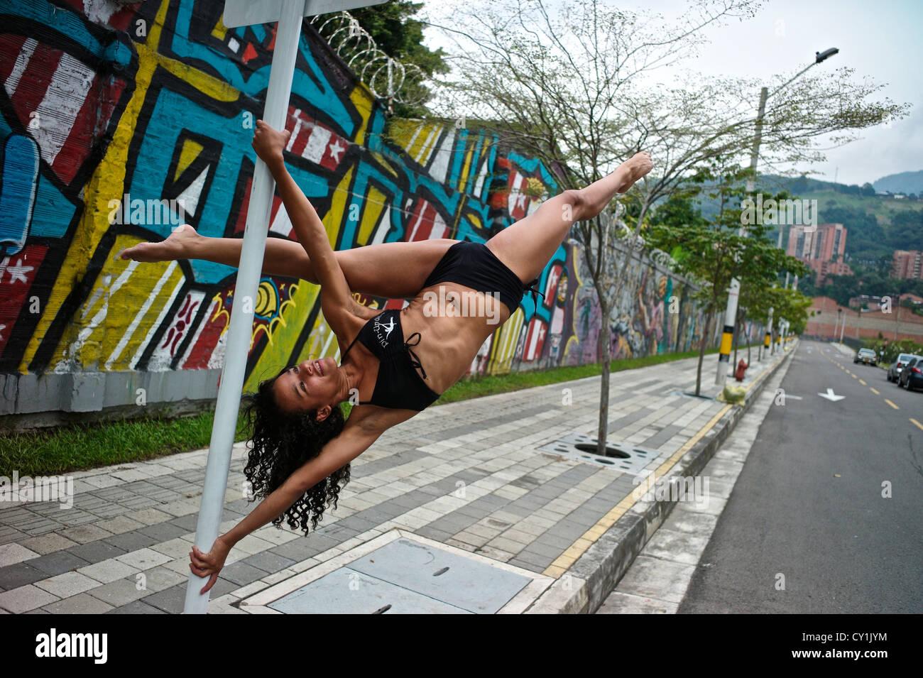 Eine Tänzerin führt eine Pose auf einem Mast im Freien neben einem urban Graffiti. Stockfoto
