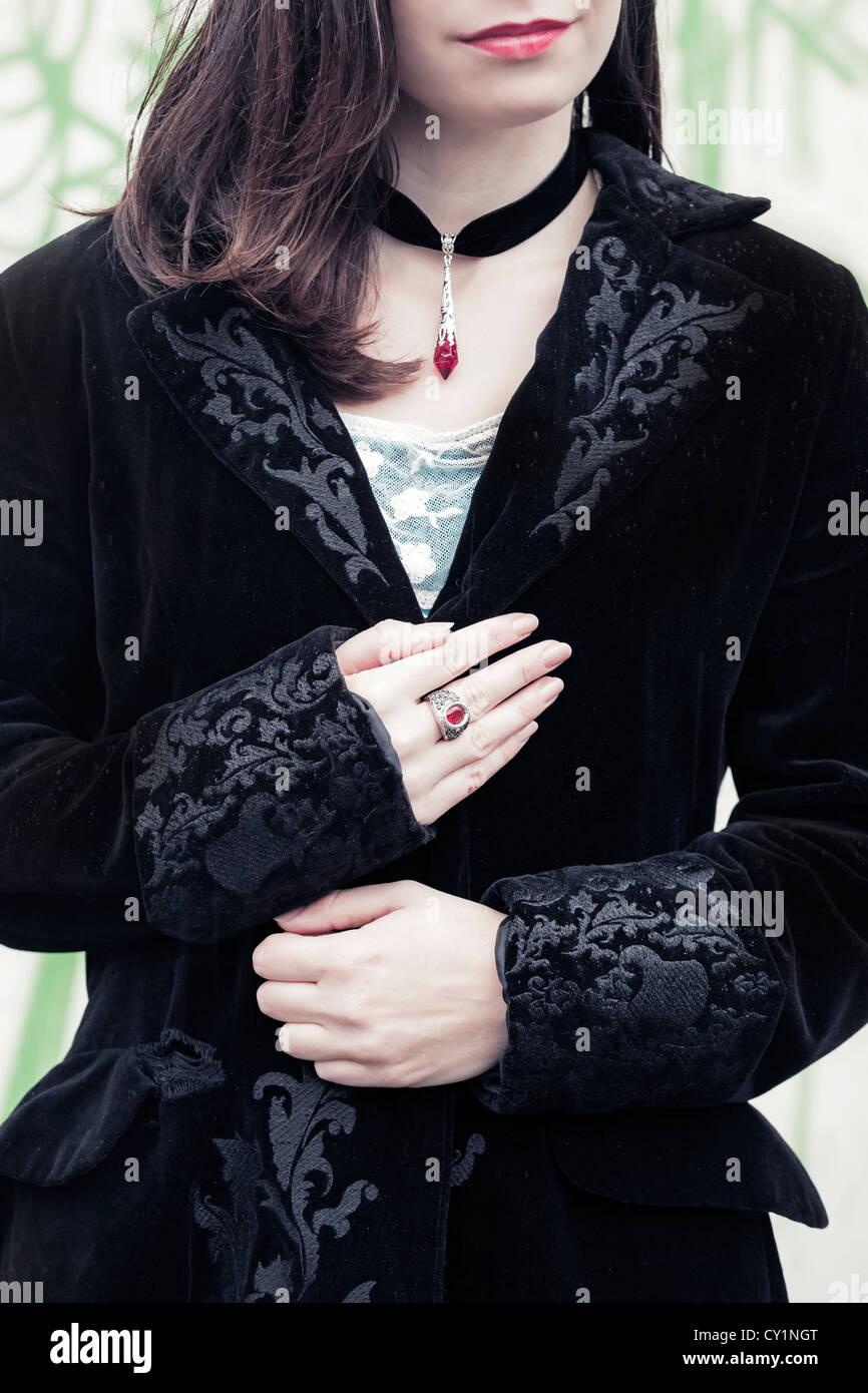 eine Frau in einem schwarzen Mantel mit einem roten ring Stockbild