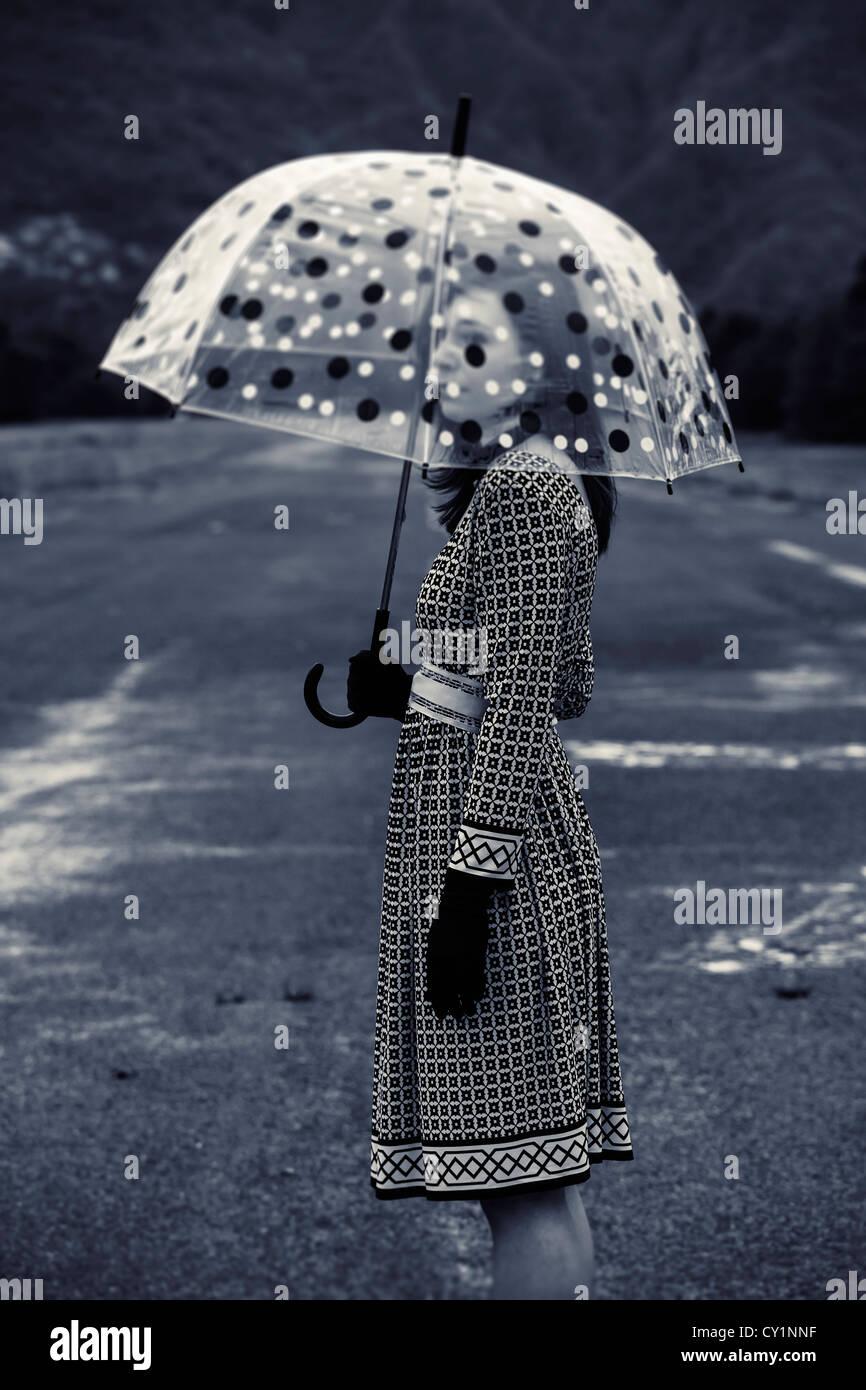 eine Frau in einem schwarzen und weißen Kleid mit einem Vintage Schirm Stockbild