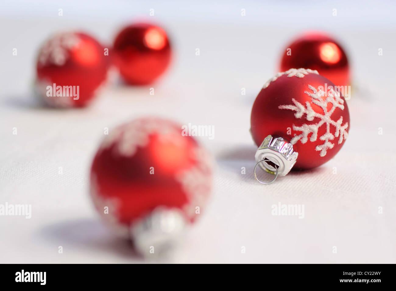 Kleine rote Weihnachtskugeln auf einer weißen Tischdecke Stockbild
