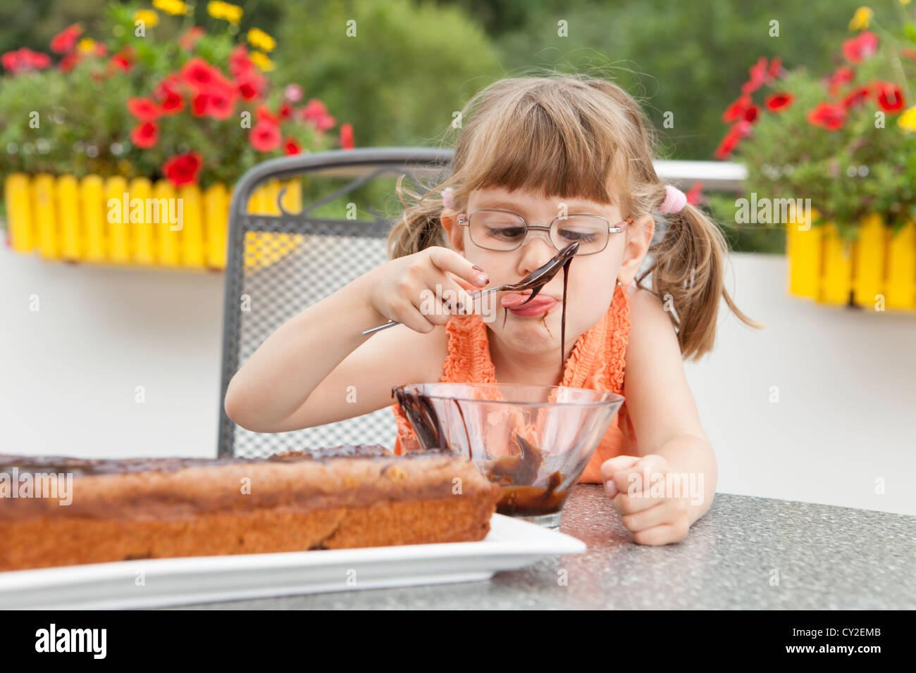 Kleines Mädchen schmücken den Schokoladenkuchen Stockbild