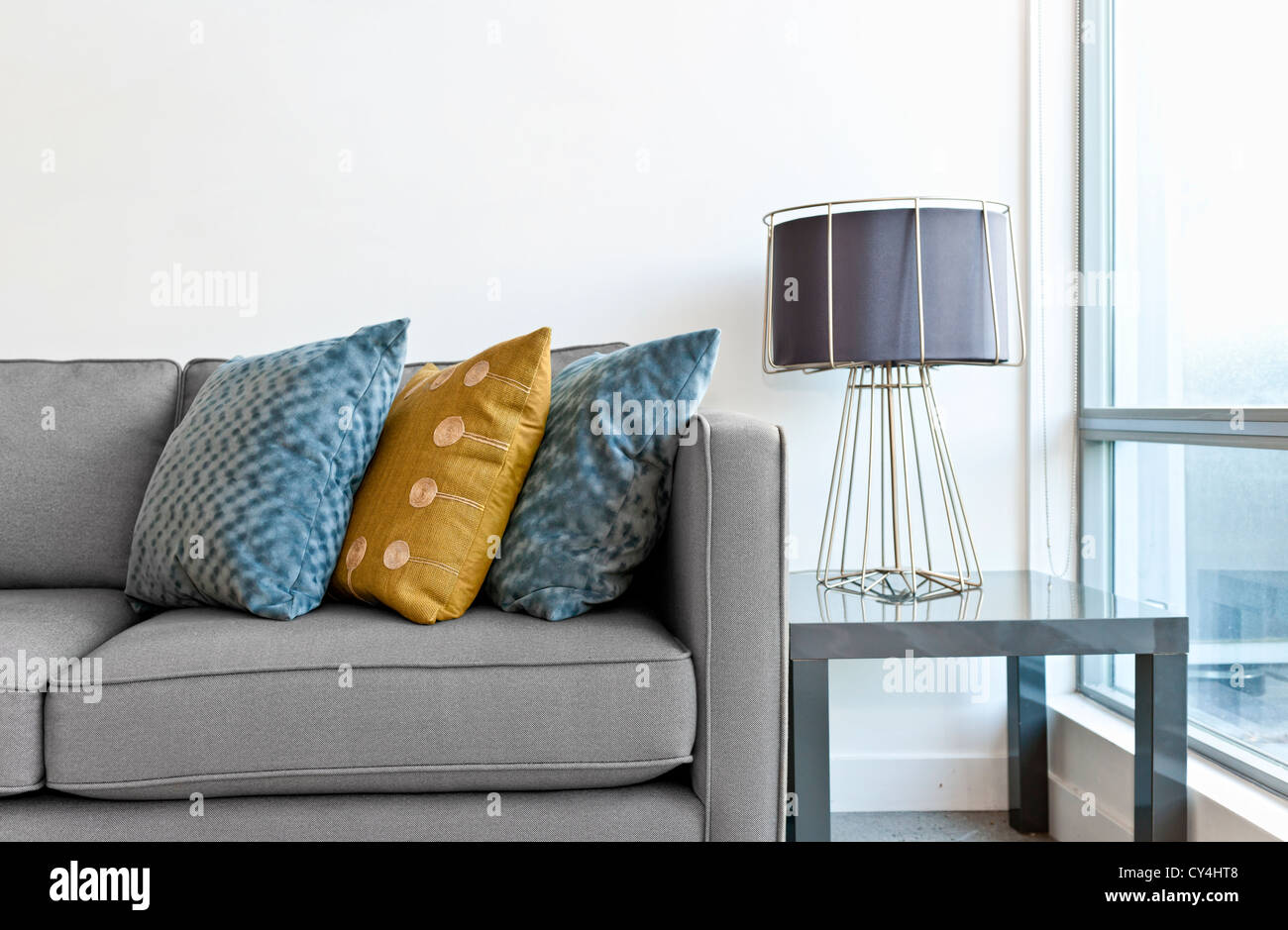 Raumgestaltung mit Couch, bunten Kissen und Lampe auf Tisch Stockbild