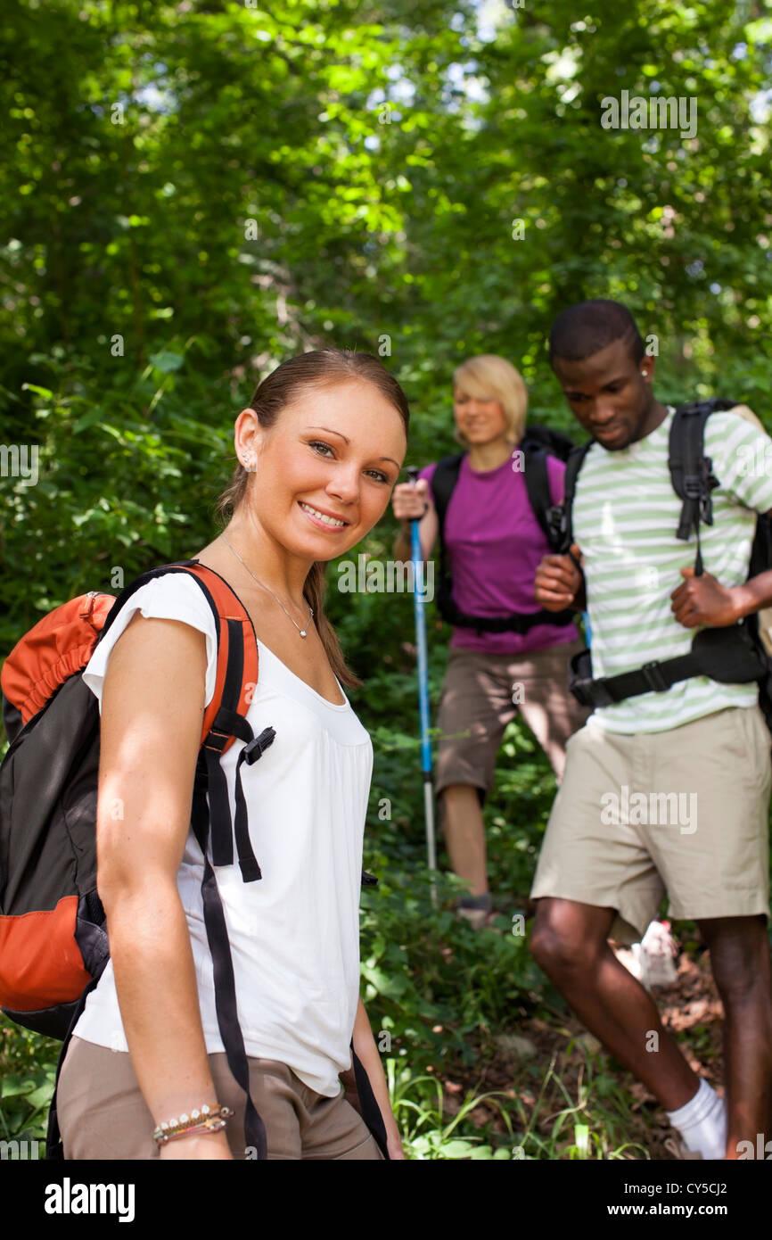 Gruppe von Mann und Frau beim Wanderausflug in Wäldern, mit Blick in die Kamera und lächelnde Frau. Taille Stockbild