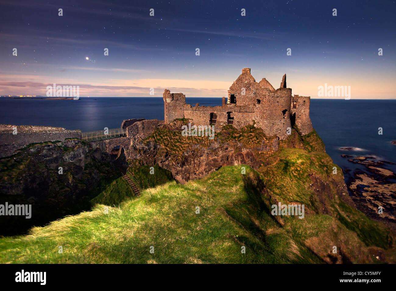 Dunluce Castle gefangen in der Nacht im Mondlicht. Stockfoto