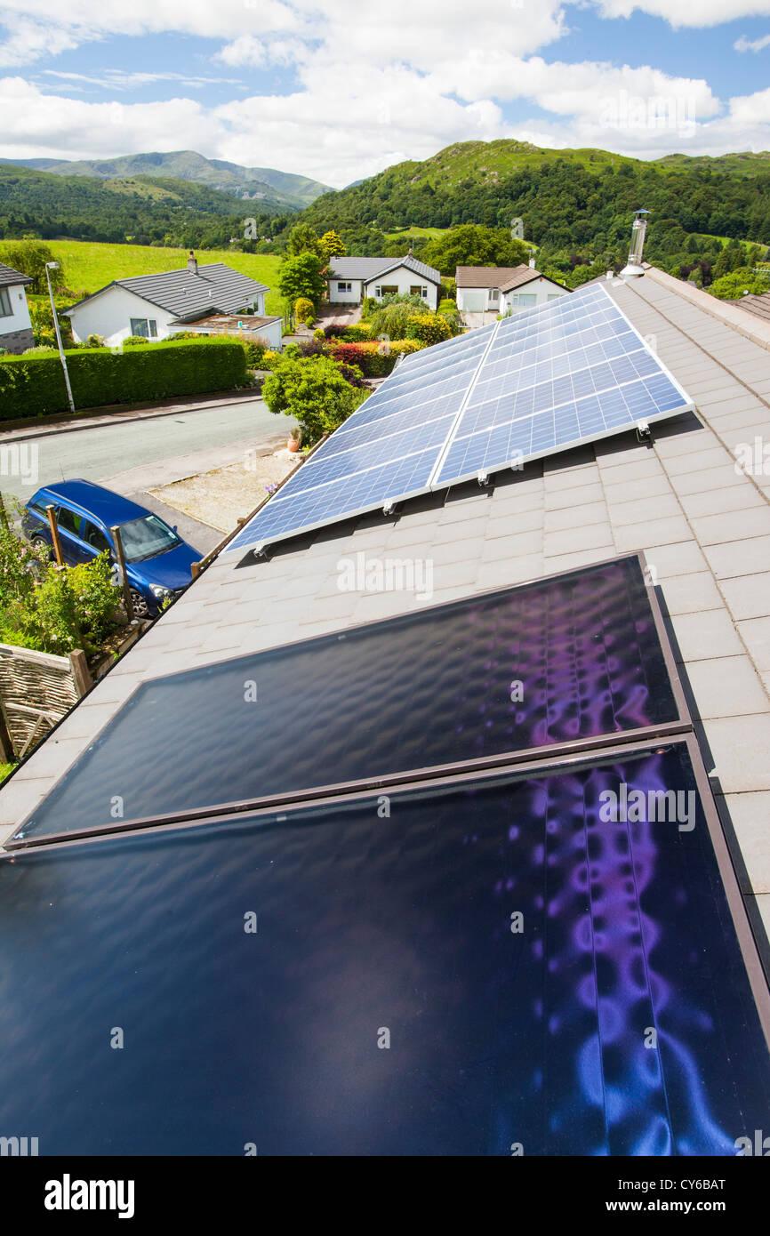 Thermische Sonnenkollektoren Für Warmwasser Mit Solar PV Schalttafeln  Hinter Ein Haus Heizung Dach In Ambleside,