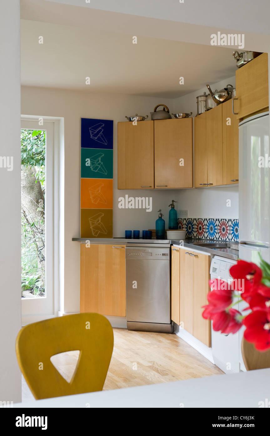 Holz ausgestattete Küche mit Edelstahl-Arbeitsplatte und bunten ...