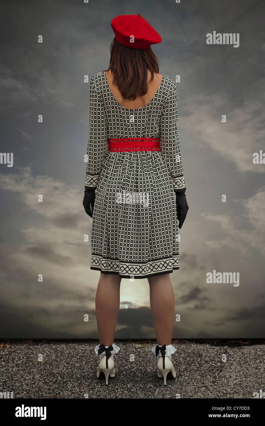 eine Frau in einem schwarzen und weißen Kleid mit einer roten Kappe steht an der Kante eines Dachs Stockbild