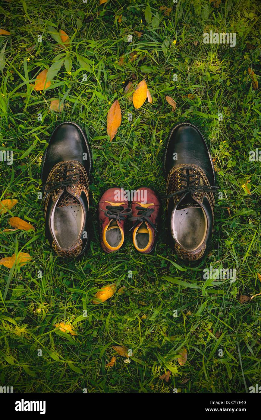 Vater und Kind - Mannes Schuhe und ein paar Schuhe des Kindes Stockbild