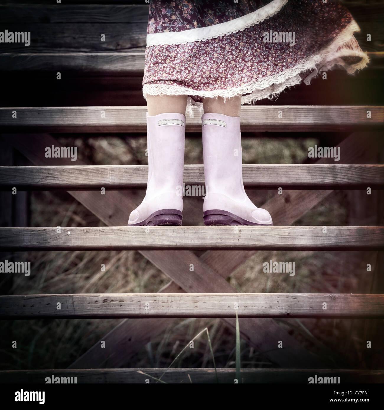 eine Mädchen in Gummistiefel steht auf Holzstufen Stockbild