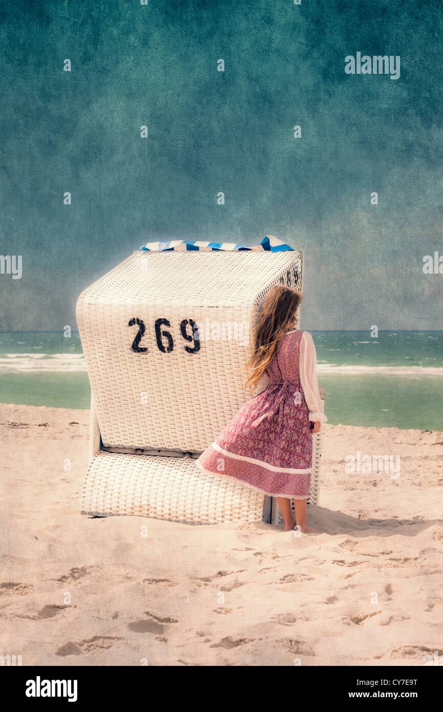 ein Mädchen und ein Strandkorb Stockbild