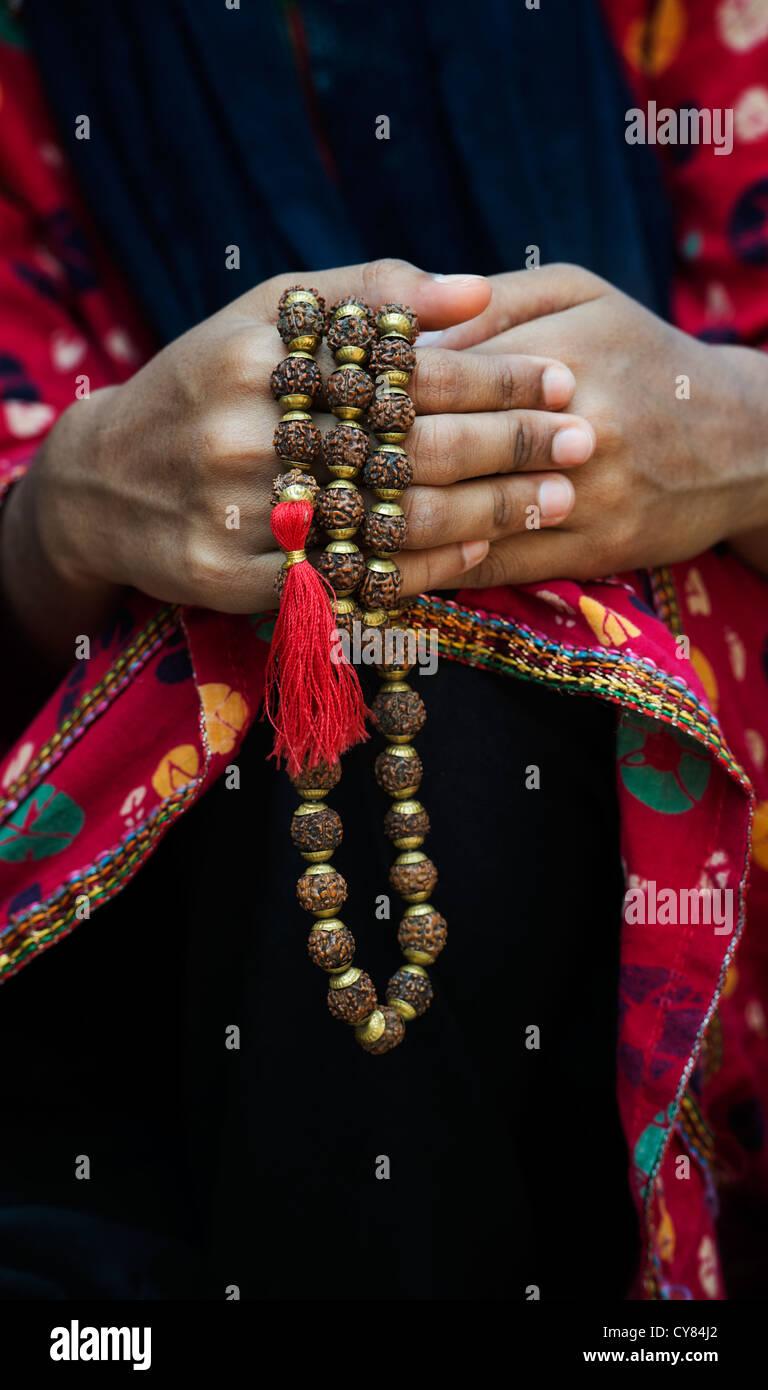 Indische Mädchen Händen mit indischen Rudraksha / Japa Mala Gebetskette. Indien Stockfoto