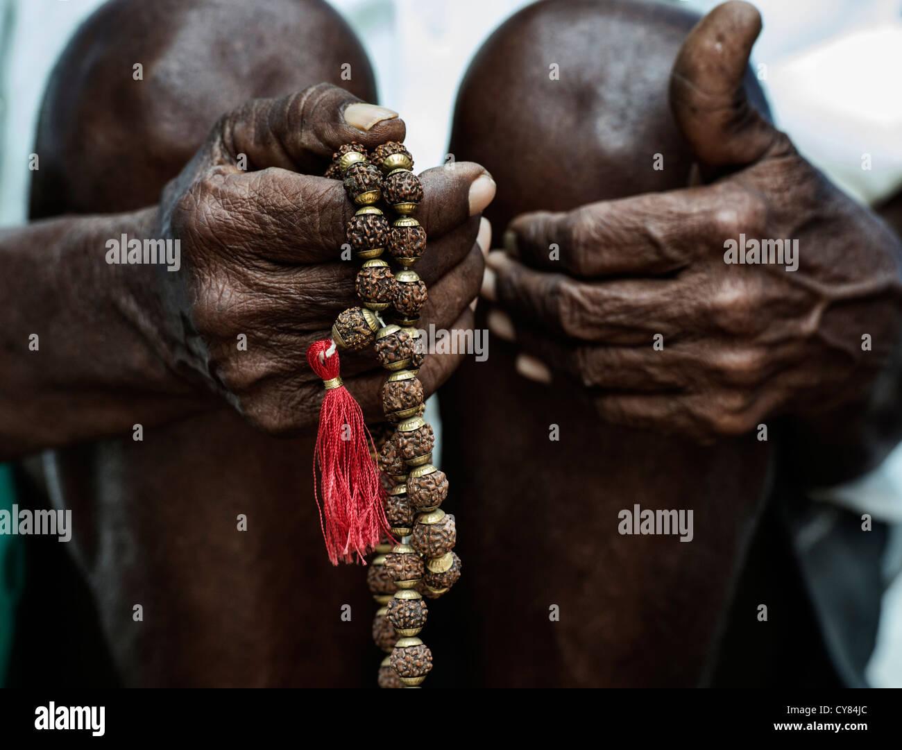 Alten indischen mans Hand mit indischen Rudraksha / Japa Mala Gebetskette Stockfoto