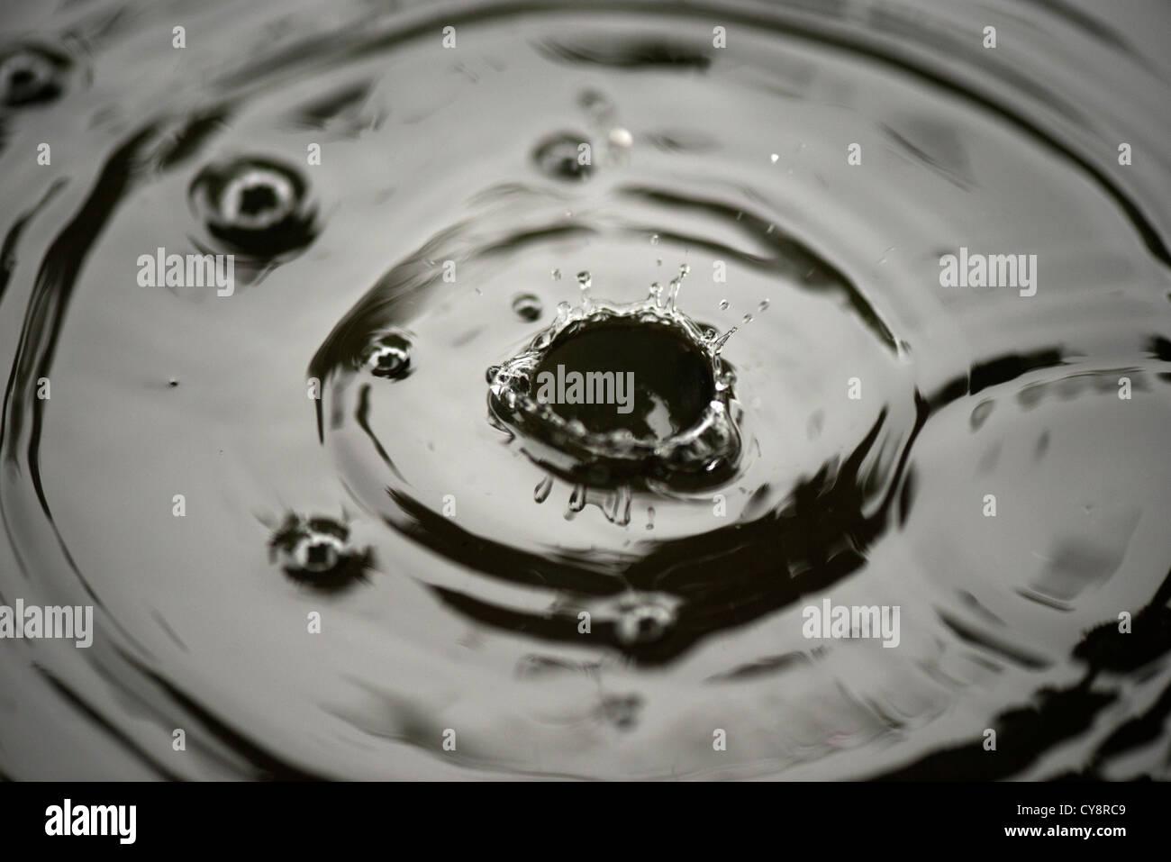 Tropfen auf Wasser spritzt Stockbild