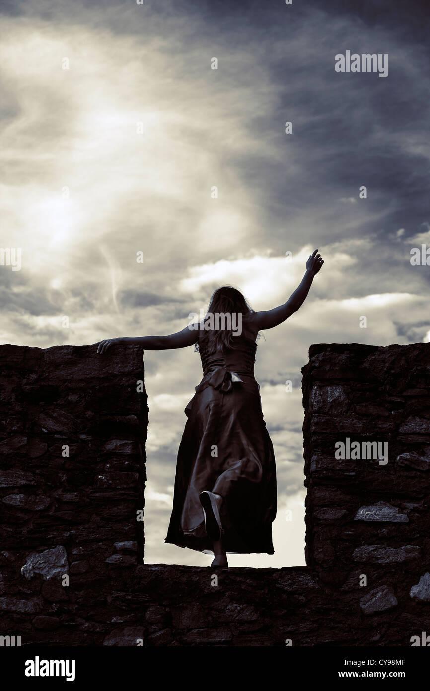 eine Frau an einer Wand aus dem Boden schießen Stockbild