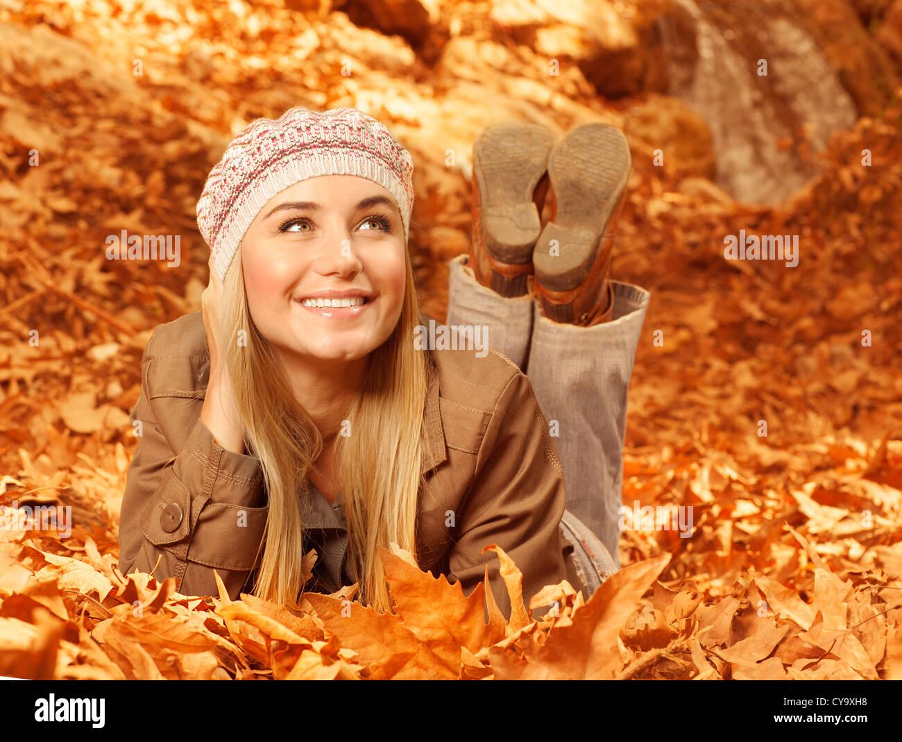 Bild von ziemlich fröhliche Frau legte sich auf dem Boden trocken herbstliche Laub, nette junge Dame, die Spaß Stockbild