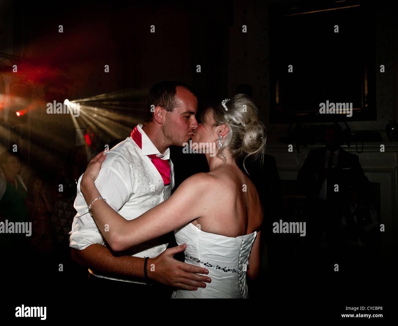 Eine Braut und Bräutigam küssen sich während des ersten Tanzes am Tag ihrer Hochzeit romantisch. Stockbild