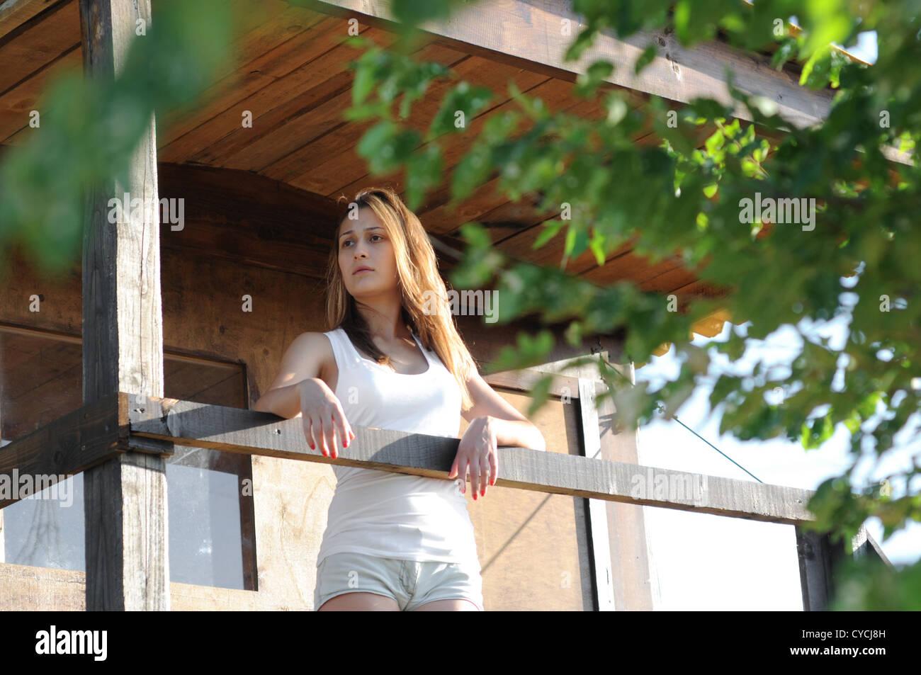 Frau auf dem Balkon eines Holzhauses. Stockbild