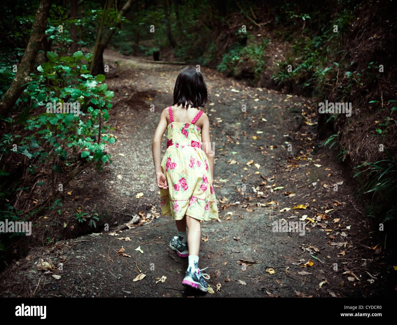 Mädchen-Schritten bergauf auf Waldweg. Stockbild