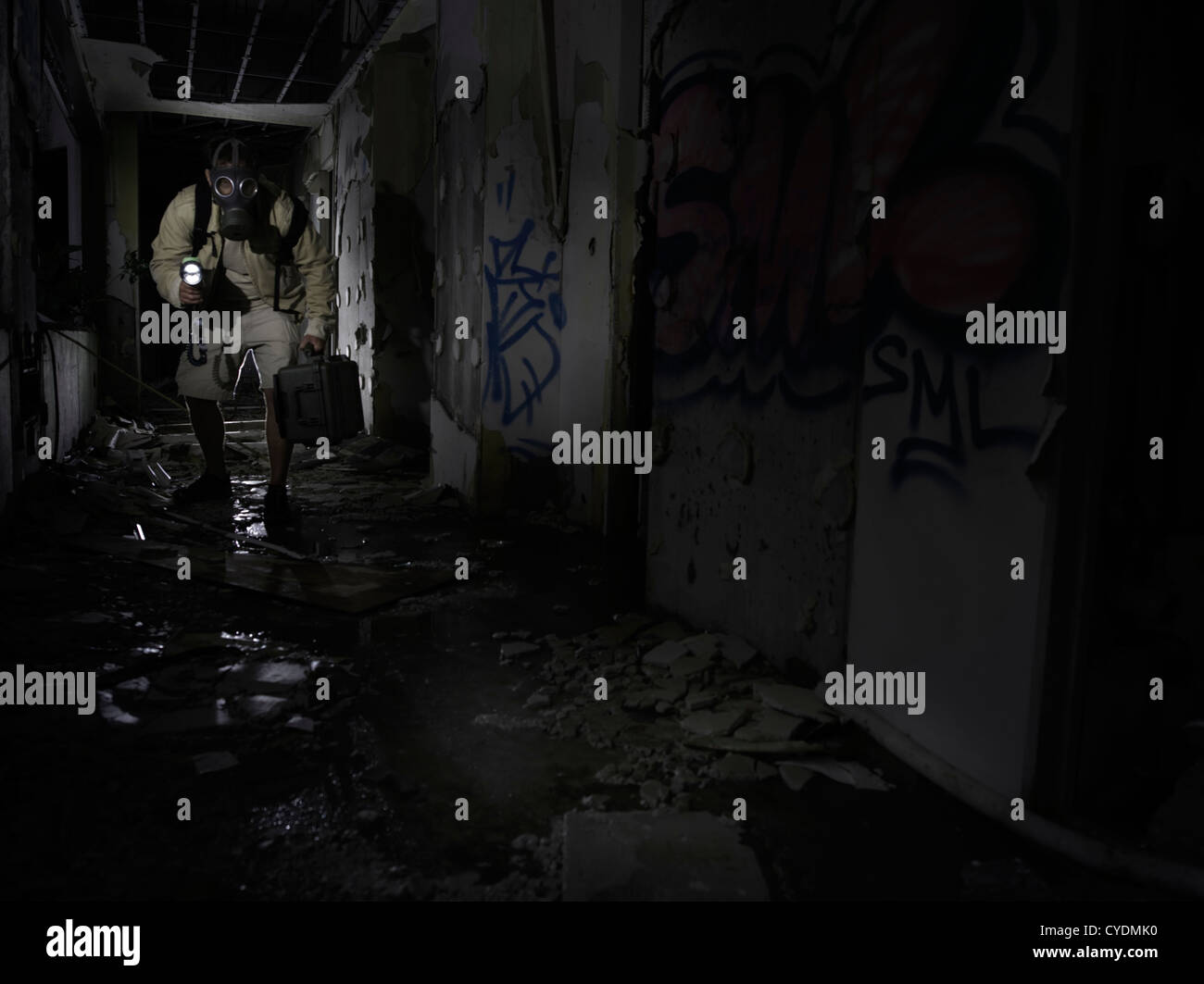 Mann mit Gasmaske und mit Taschenlampe untersucht ein verlassenes Gebäude / Tatort Stockbild