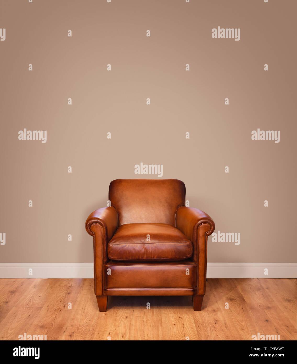 Ledersessel auf einem Holzfußboden gegen einen einfarbigen Hintergrundwand mit vielen Exemplar. Die Mauer hat Stockbild