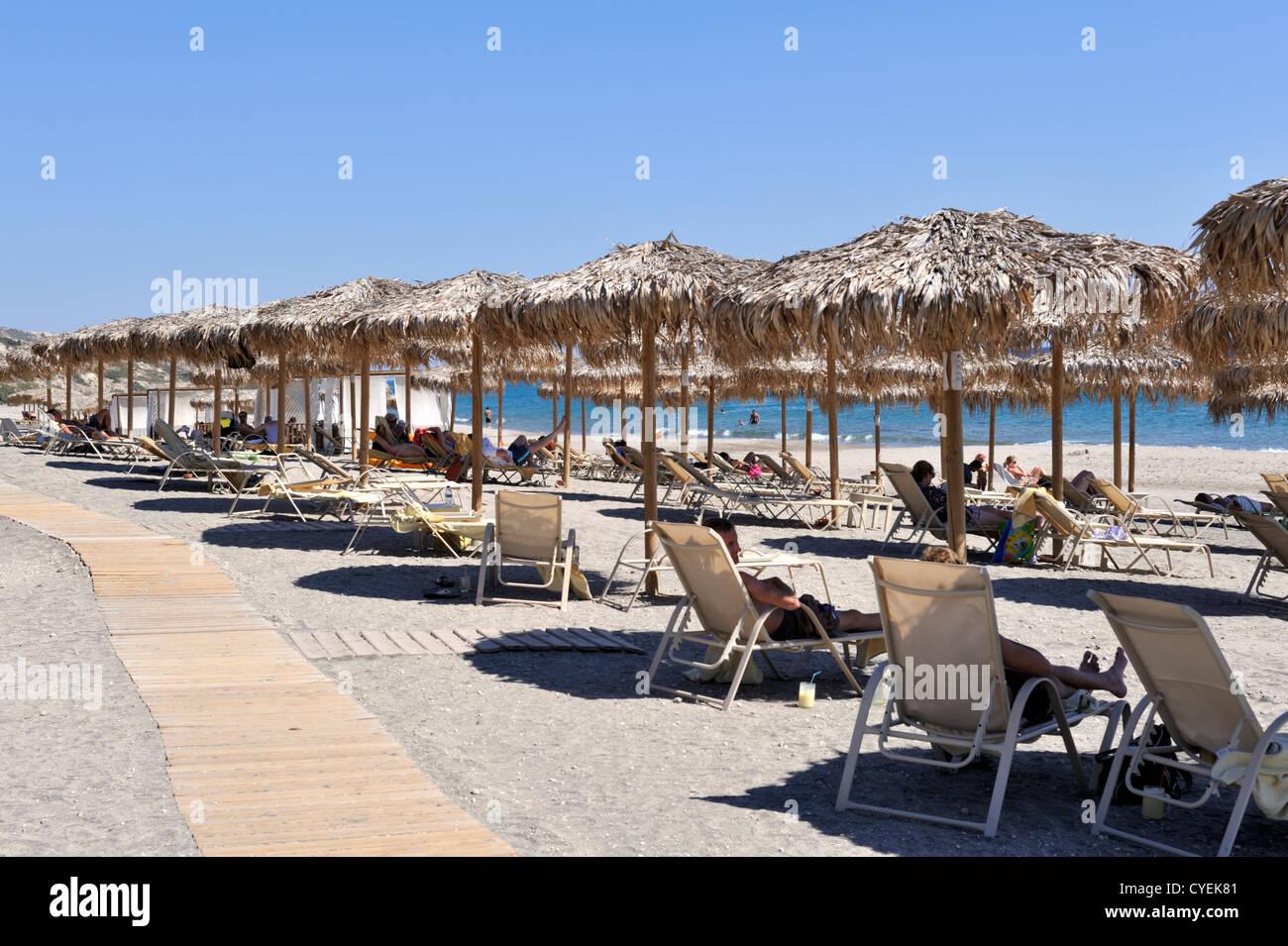 Sandstrand auf dem Seeweg mit strohgedeckten Sonnenschirmen, an Bord gehen und Touristen, Insel Kos, Griechenland Stockbild