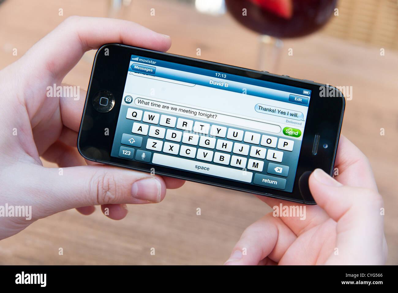 Senden von SMS-Nachricht auf dem Apple iPhone 5 Stockbild