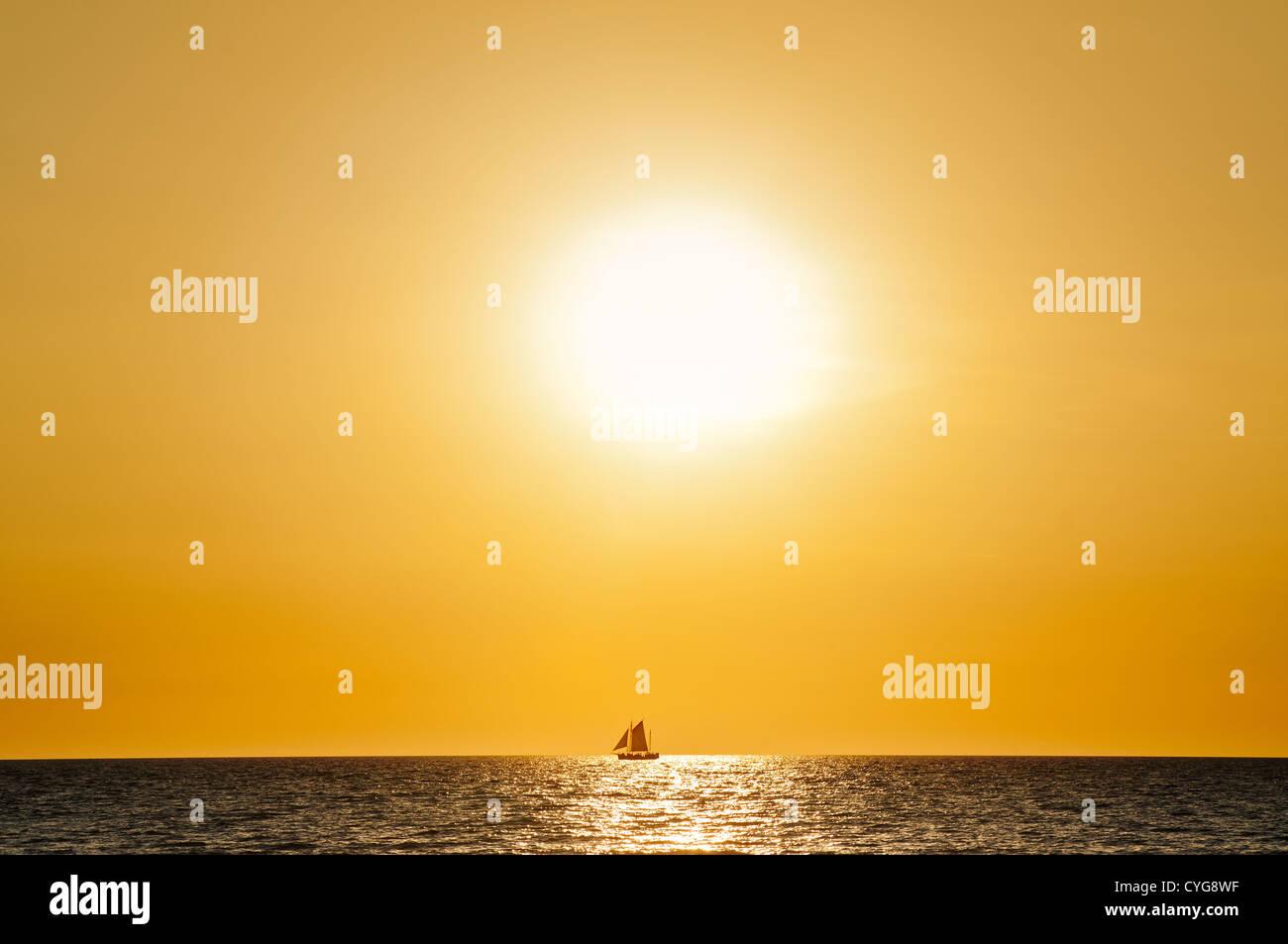 Segelboot vor der untergehenden Sonne am Horizont. Stockbild