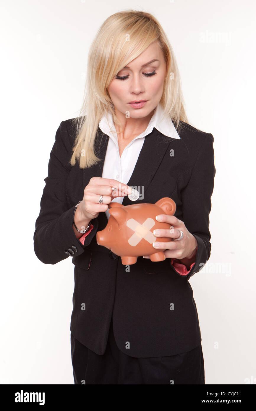 Frau betrachtet die fehlerhaften Zustand ihrer Finanzen, wie sie eine einzelne Münze in ein Sparschwein mit Stockbild