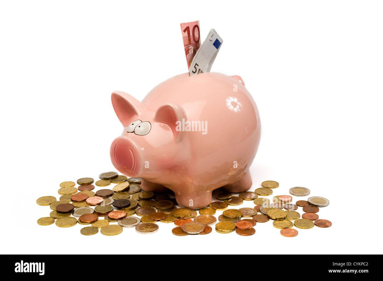 Eine rettende Schwein steht zwischen einer Menge von Euro-Münzen Stockbild