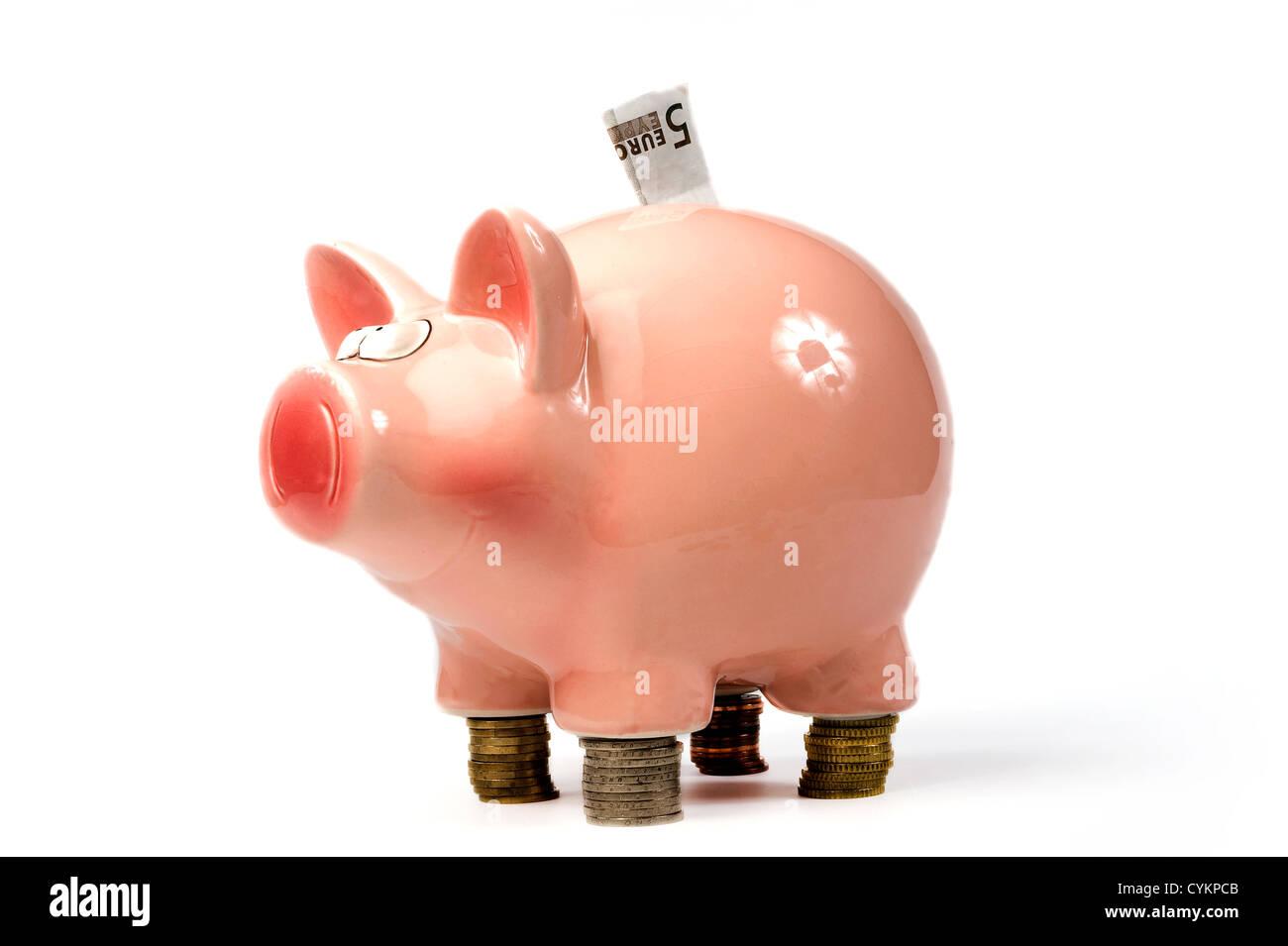 Eine rettende Schwein steht auf geheftete Euro-Münzen Stockbild