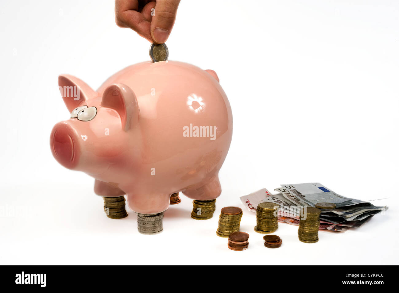 Eine Hand ist eine 2-Euro-Münze in eine rettende Schwein setzen. Stockbild