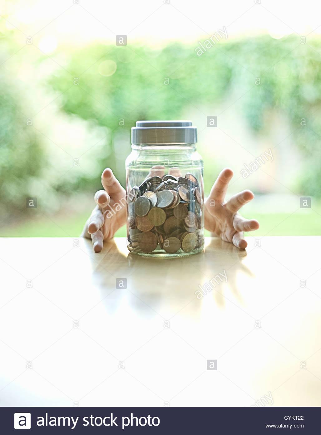 Hände greifen Jar des Wandels Stockbild