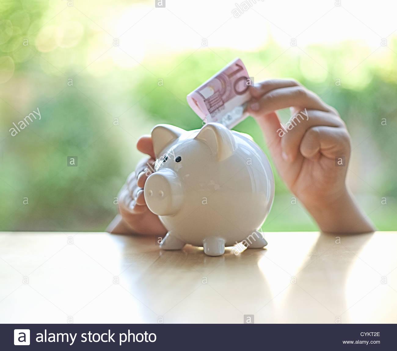 Putting-Euro-Schein im Sparschwein zu hängen Stockbild