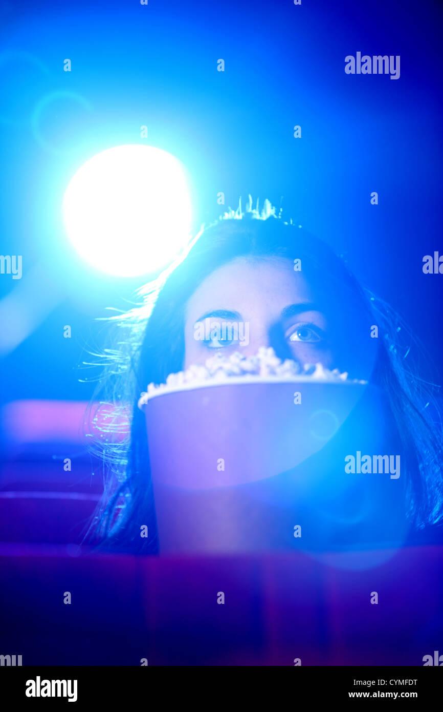 eine hübsche junge Frau sitzt am Theater, sie hat Angst und versteckt sich hinter eine Kiste mit popcorn Stockbild