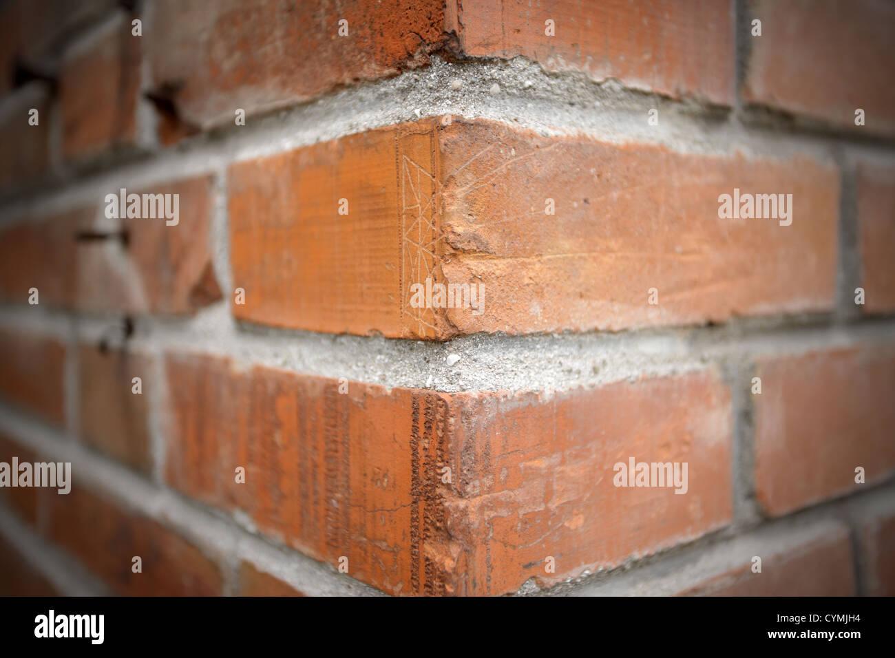 Die Ecke von einer roten Backsteinmauer. Breite Schuss. Stockbild