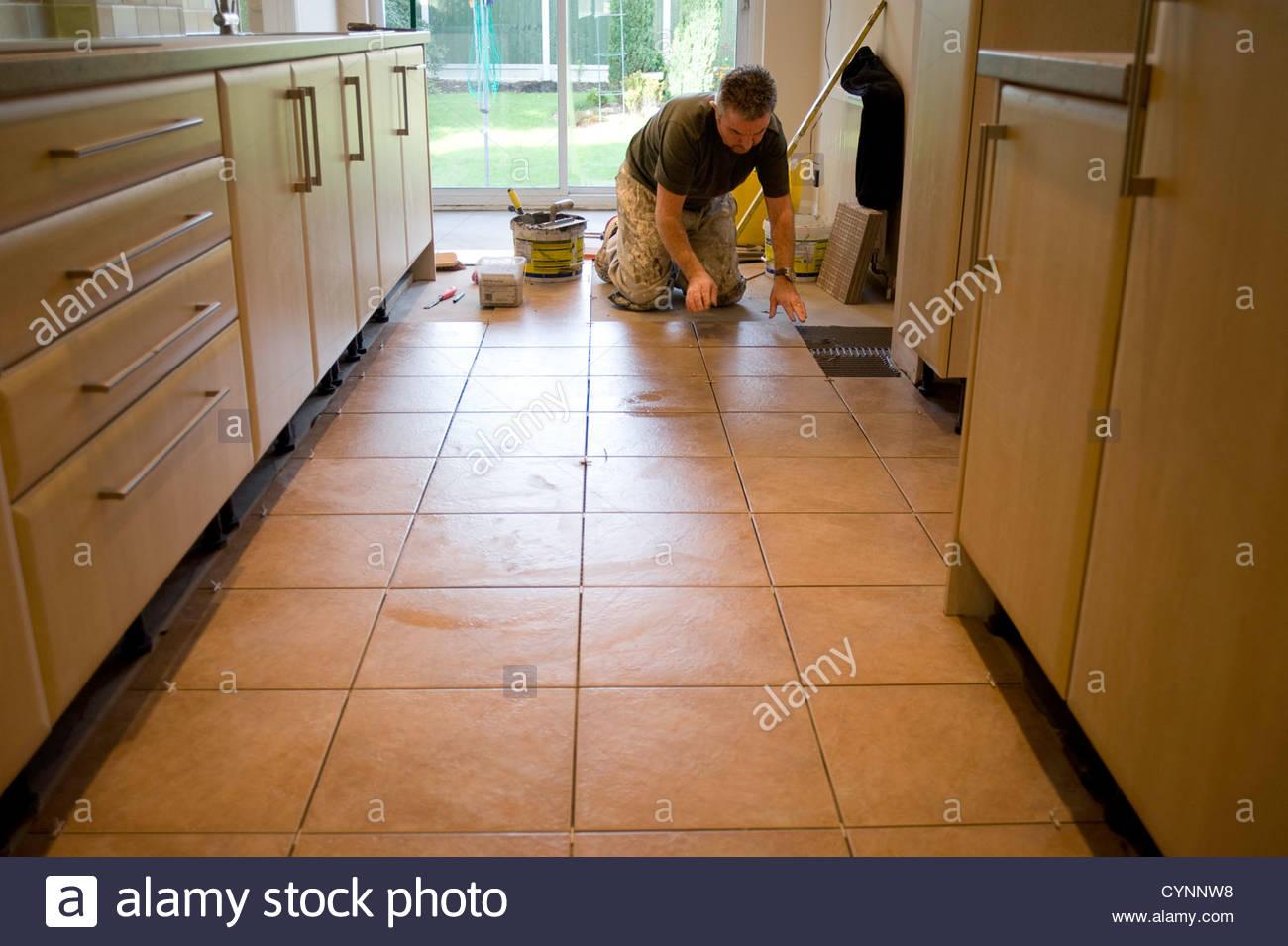 Auf den Knien den Küchenboden Fliesen Fliesenleger Stockfoto, Bild ...