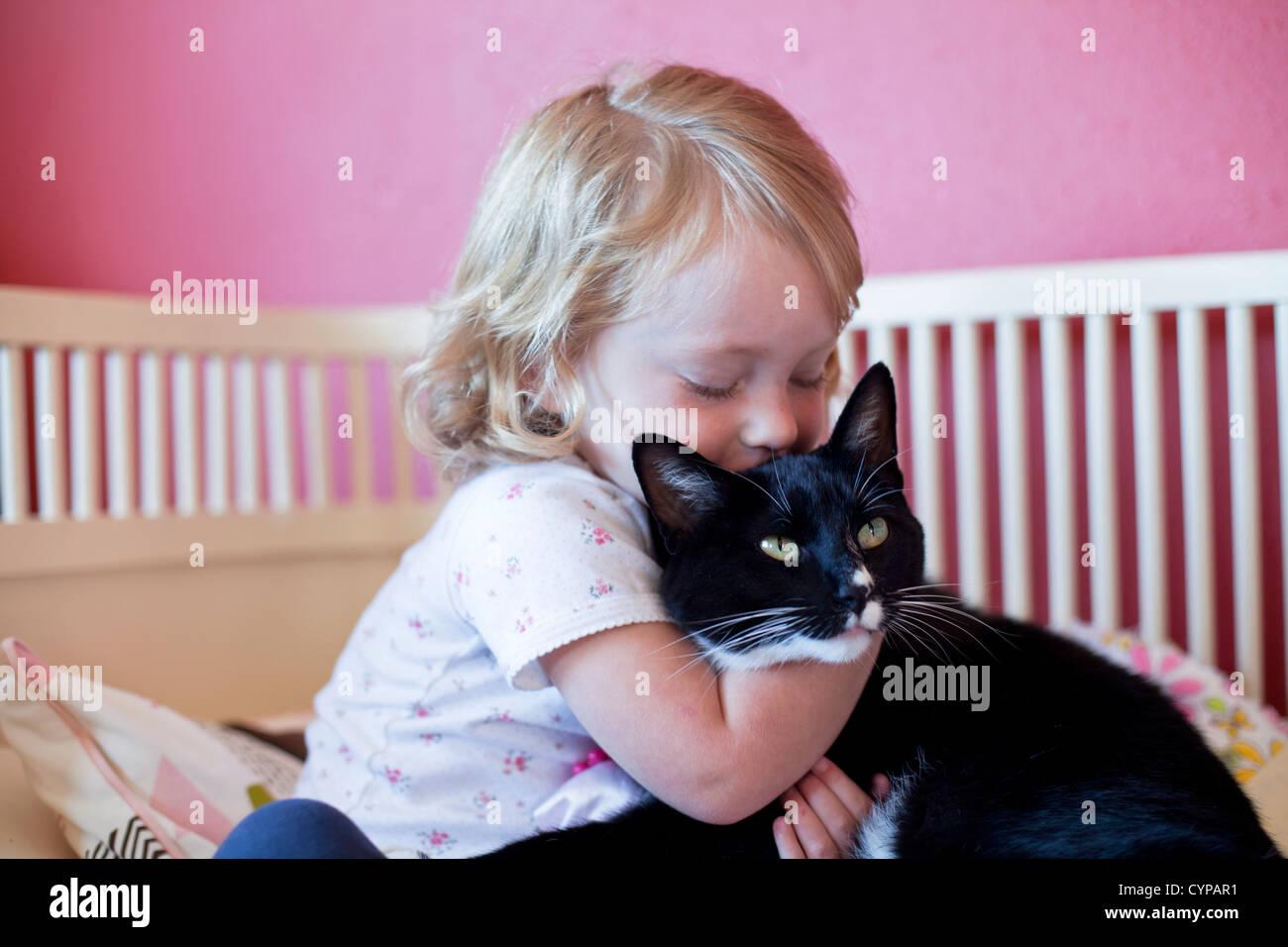 Kleinkind Mädchen umarmt ihre Katze. Stockfoto