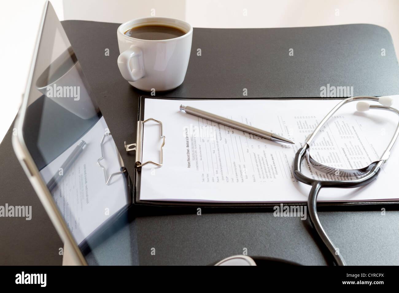 Medizinische Aufzeichnung Formen, Stethoskop und Tablet PC auf dem Schreibtisch Stockbild