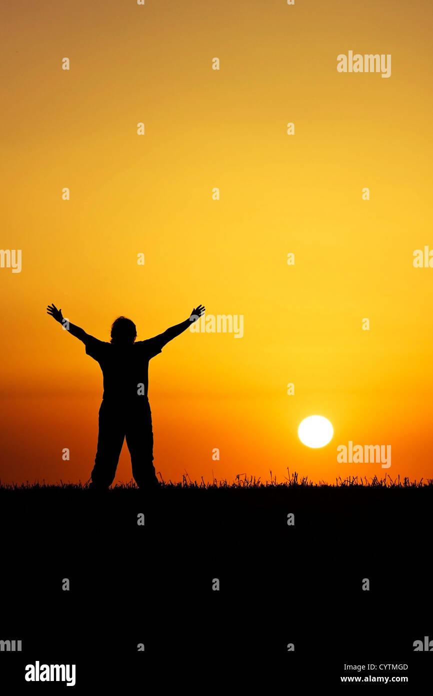 Eine Person mit den Händen in der Luft vor einem schönen roten Sonnenuntergang Stockbild