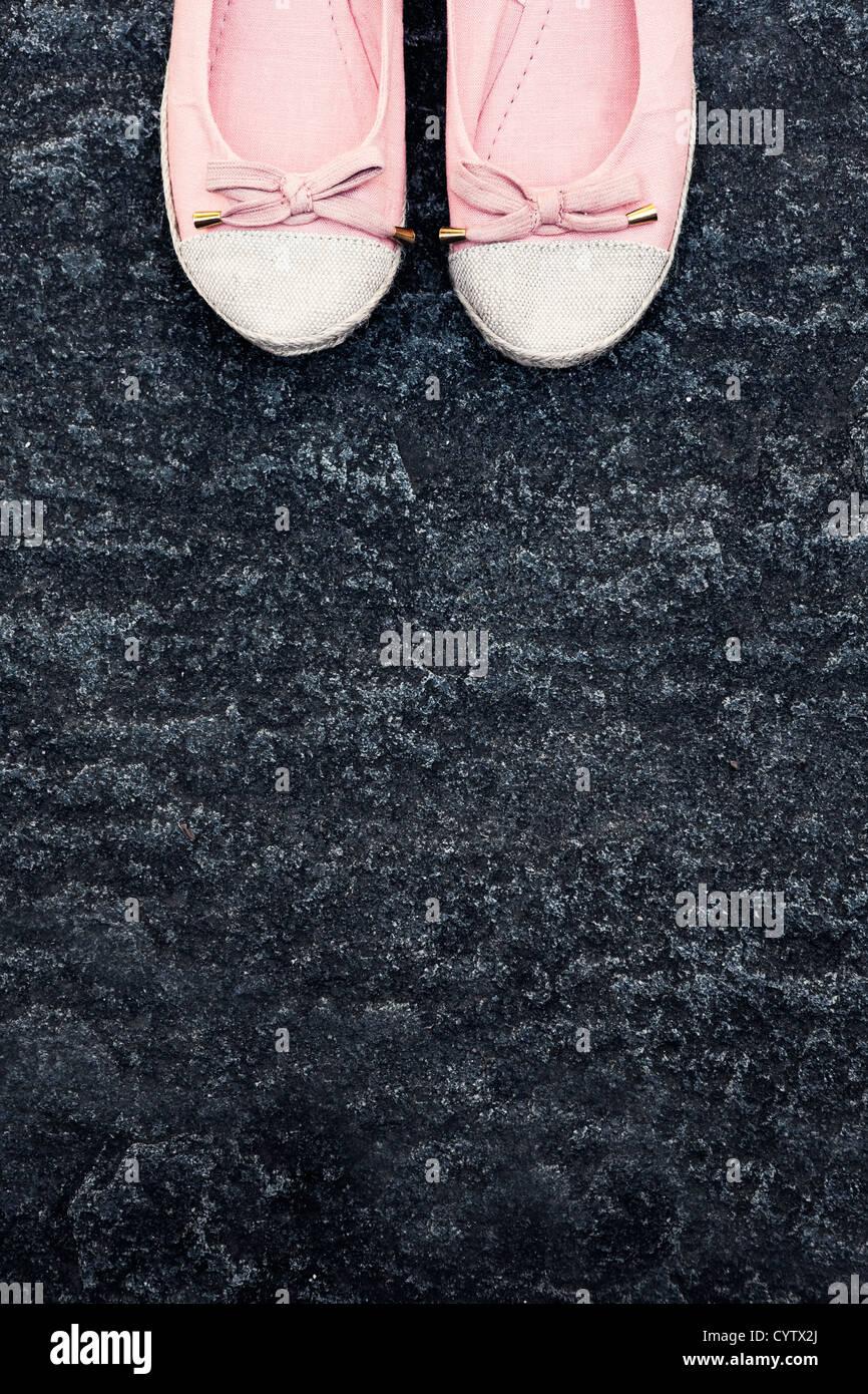 zwei rosa Schuhe auf einem Steinboden Stockbild