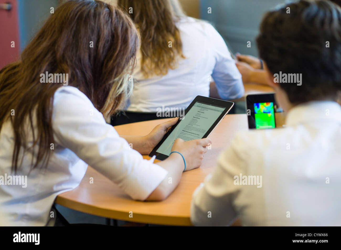 Schulmädchen mit iPad während einer Unterrichtsstunde an einem umfassenden Gymnasium Wales UK Stockbild
